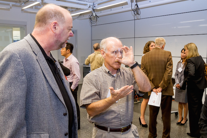 Commander Ken Bowersox, ret., examines the lens material for eVision Smart Optics' electronically tunable lenses, while Tony Van Heugten, eVision's Chief Technology Officer, explains the liquid crystal technology.