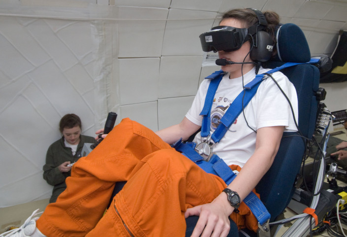 Kara Beaton, seated in the experiment's tilted chair, performed the virtual navigation task with and without the help of the tactile cueing of her orientation. Kate Montgomery, seated on floor, operates the experiment. Photo by NASA.